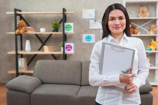 Sympathique femme psychologue debout dans son bureau avec le presse-papier et un crayon Photo gratuit