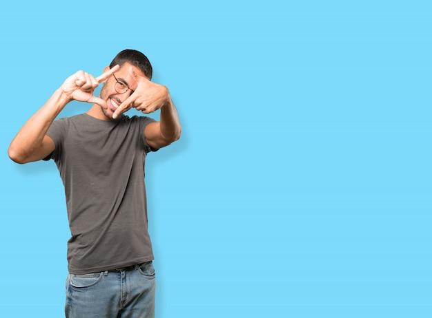Sympathique jeune homme faisant un geste de prendre une photo avec les mains Photo Premium