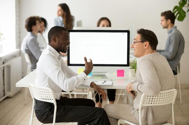 Sympathique souriant divers collègues masculins ayant une conversation agréable au travail Photo gratuit