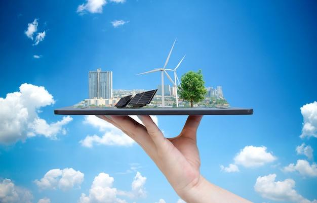Système écologique de l'énergie solaire dans la ville sur la main tenant la tablette Photo Premium