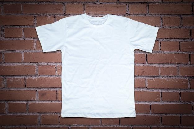 T-shirt blanc sur fond de mur de brique. Photo Premium