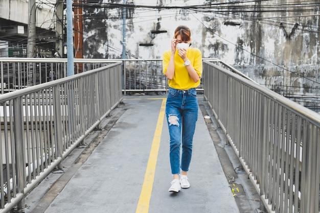 T-shirt jaune de femme asiatique portant le masque de protection respiratoire n95 contre la pollution de l'air se promenant à bangkok Photo Premium