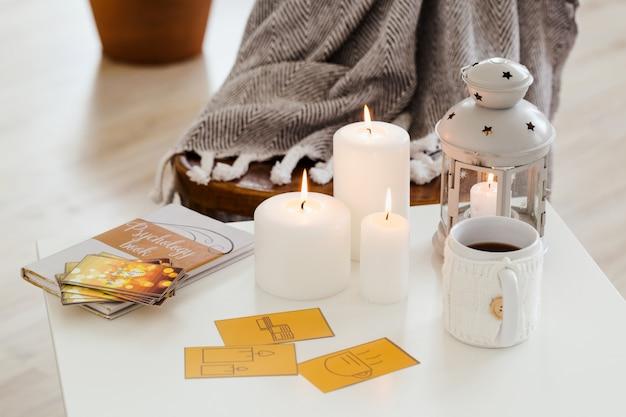 Sur La Table Basse Sont Des Cartes, Un Livre, Une Tasse De Thé Chaud, Des Bougies. Composition En Gros Plan. Photo Premium