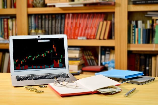 Sur la table, bitcoins, cahiers, lunettes et ordinateur doré avec graphique boursier à l'écran Photo Premium