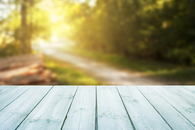 La table bleue sur fond de route forestière floue peut être utilisée pour afficher ou monter votre produit. Photo Premium