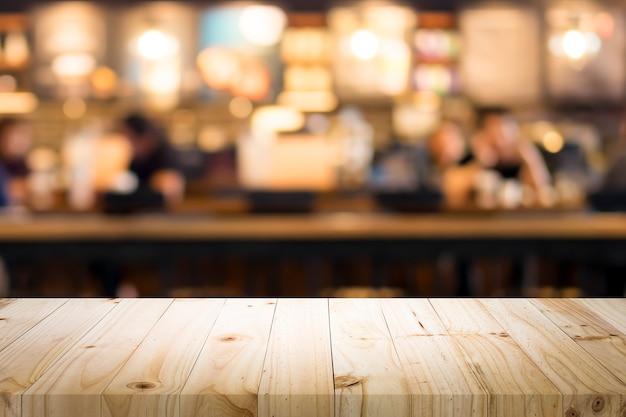 Table en bois avec arrière-plan flou de café. Photo Premium