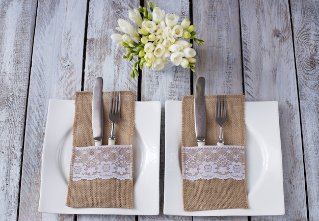 Sur une table en bois blanc, deux assiettes, fourchettes et couteaux, des fleurs dans un vase - un fond de fête (anniversaire, mariage, 8 mars, dîner romantique) Photo Premium