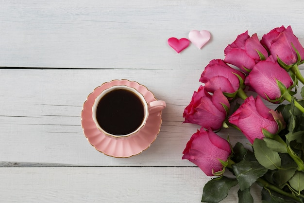 Sur une table en bois blanche roses roses et café dans une tasse rose et deux coeurs roses de sati Photo Premium