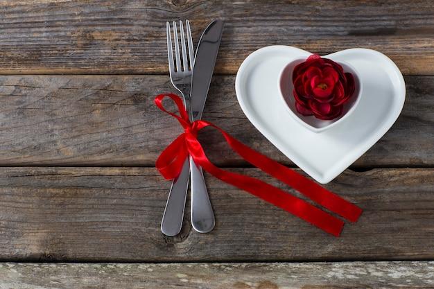 Sur une table en bois, deux assiettes en forme de cœur, un bouton de rose rouge et des couverts noués avec un ruban rouge Photo Premium