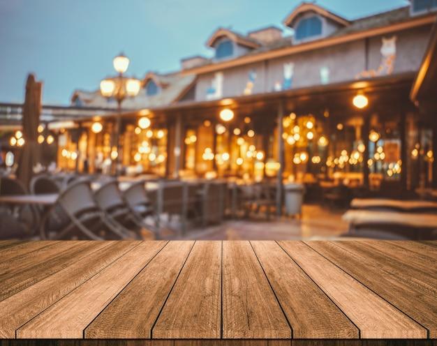 Table En Bois Devant Le Restaurant Floue Abstrait Lumières Photo Premium