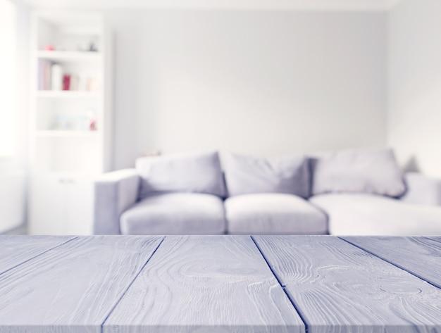 Table en bois grise devant le canapé flou blanc dans le salon Photo gratuit