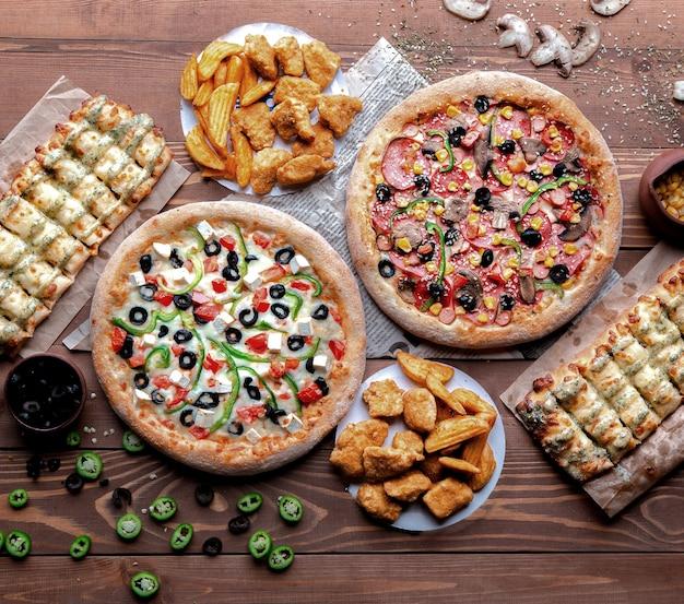 Table en bois avec des pizzas et des snacks Photo gratuit