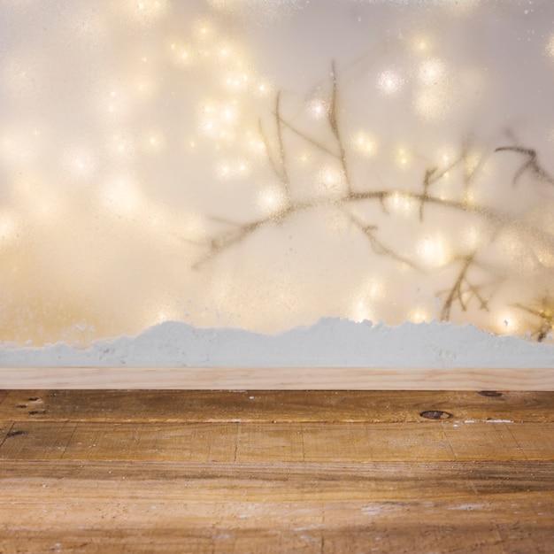 Table en bois près de la berge de la neige, branche de la plante et guirlandes Photo gratuit