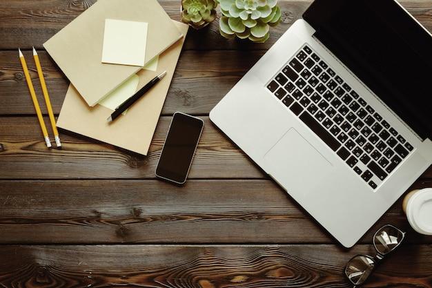 Table en bois sombre avec ordinateur portable, vue de dessus du bloc-notes Photo Premium