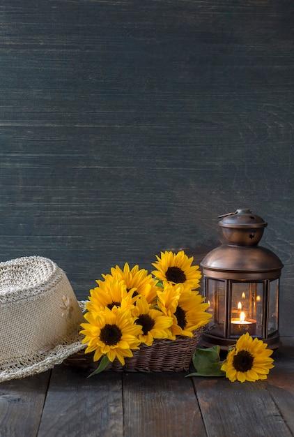 Sur une table en bois sombre, une vieille lanterne avec une bougie, un bouquet de tournesols et un chapeau de paille Photo Premium