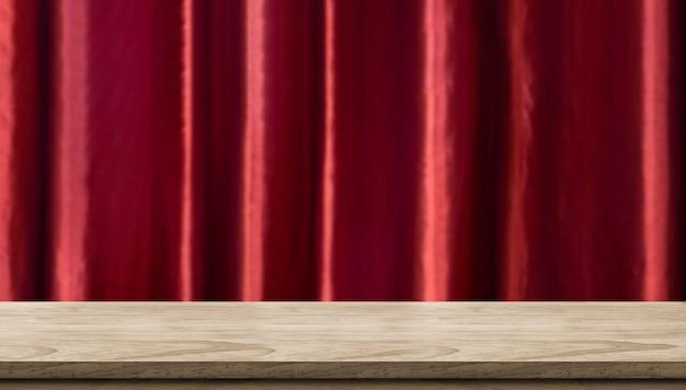 Table en bois vide et fond de rideau de luxe rouge vif floue. Photo Premium