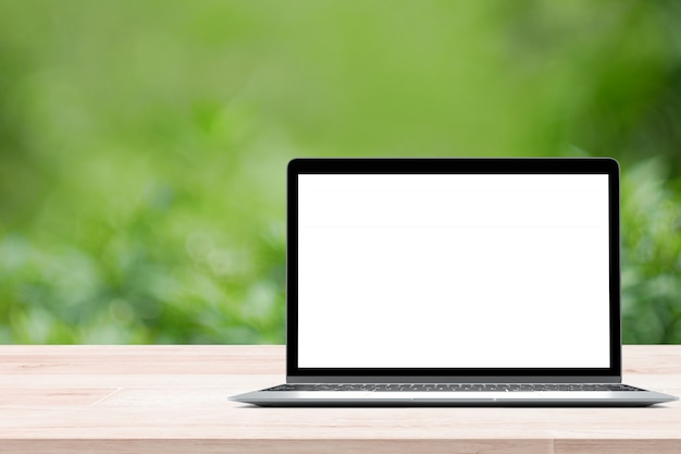 Table en bois vide avec ordinateur portable écran blanc sur fond flou vert du feuillage Photo Premium