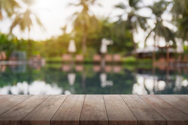 Table en bois vide et piscine floue dans le fond de la station tropicale. Photo Premium
