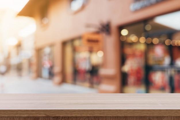 Table en bois vide et ton vintage flou défocalisé des gens de la foule au festival de la rue et au centre commercial. Photo Premium