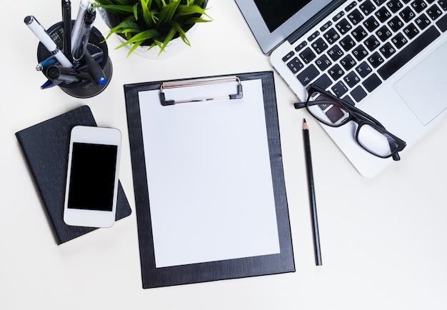 Table de bureau blanche avec beaucoup de choses dessus. vue de dessus Photo Premium