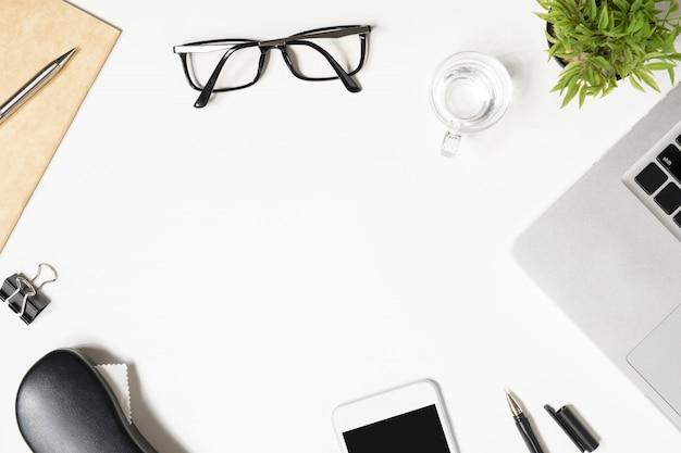 Table de bureau blanche avec beaucoup de choses dessus. Photo Premium
