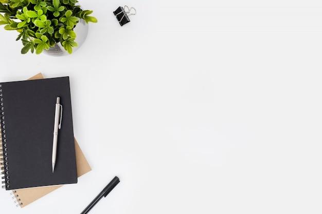 Table de bureau blanche avec cahiers et stylos. Photo Premium