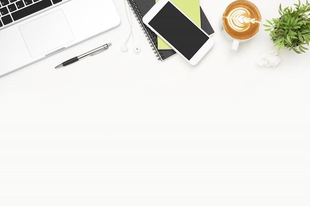 Table de bureau blanche avec ordinateur portable, smartphone, tasse de café et fournitures. Photo Premium