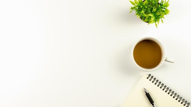 Table de bureau blanche avec une tasse à café et un stylo sur un cahier vierge Photo Premium