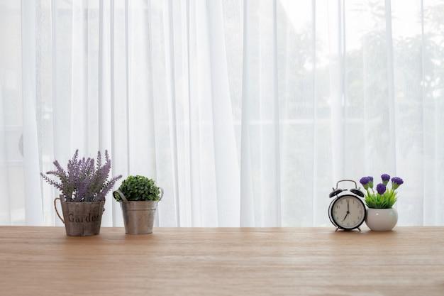 Table de bureau en bois avec fleur sur fond de rideau blanc. Photo Premium