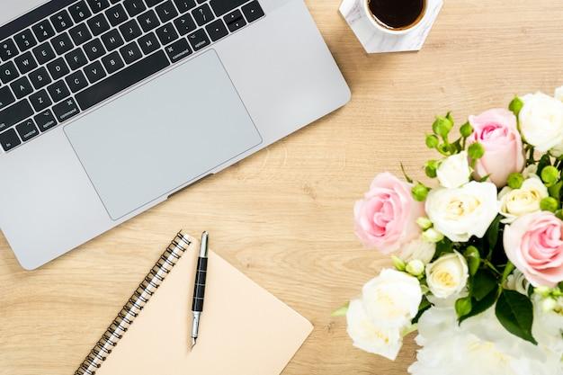Table de bureau en bois moderne avec ordinateur portable, bouquet de fleurs, tasse de café, bloc-notes en papier, stylo. Photo Premium