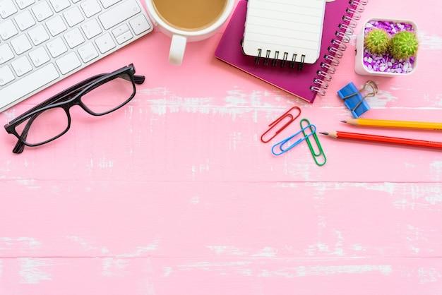 Table de bureau avec espace de travail et accessoires de bureau sur un fond en bois rose. Photo Premium