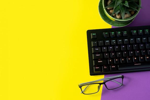 Table de bureau avec lunettes, plante et clavier. fond avec fond Photo Premium
