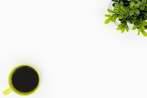 Table de bureau minimale blanche avec une tasse à café verte et un pot pour arbre. Photo Premium
