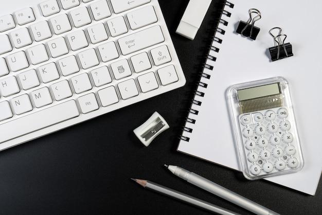 Table de bureau noir et blanc avec clavier d'ordinateur, fournitures d'affaires Photo Premium