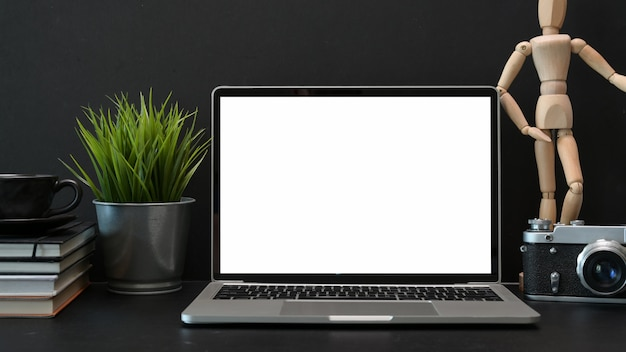 Table de bureau de photographie de bureau sombre avec un ordinateur portable à écran blanc Photo Premium