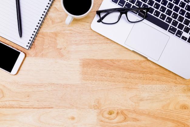 Table de bureau plat laïque du lieu de travail moderne avec ordinateur portable sur bois Photo Premium