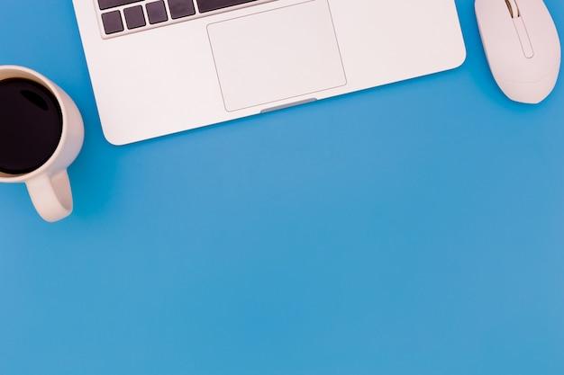 Table de bureau plat laïque du lieu de travail moderne avec ordinateur portable sur la table bleue Photo Premium