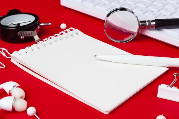 Table de bureau rouge avec bloc-notes, clavier et fournitures vierges. vue de dessus avec fond. lay plat. Photo Premium