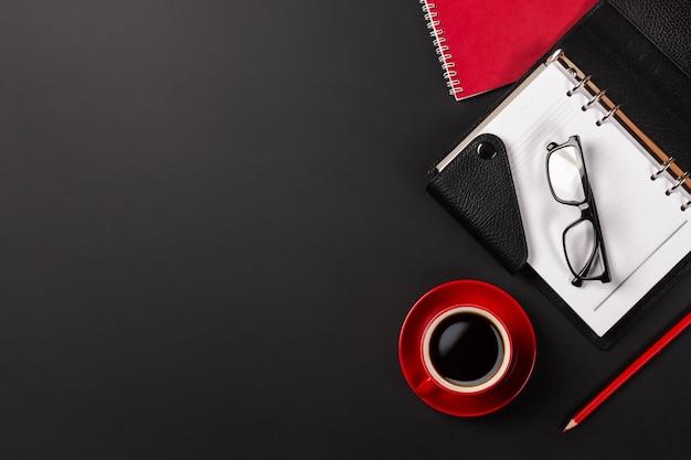 Table de bureau avec une tasse de café et des cahiers. vue de dessus avec espace de copie Photo Premium