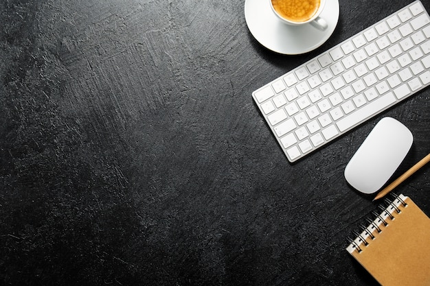 Table de bureau avec une tasse de café, clavier et bloc-notes Photo Premium