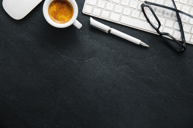 Table de bureau avec une tasse de café, clavier et bloc-notes Photo gratuit