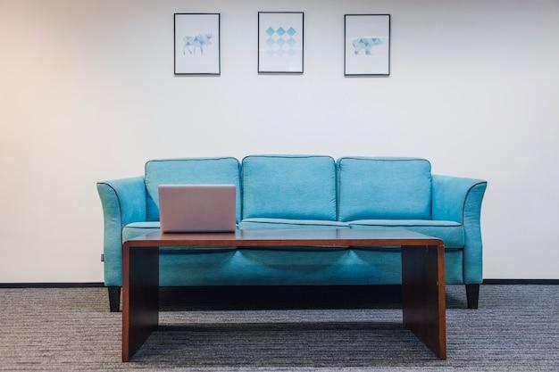 Table avec un canapé d'ordinateur portable debout dans la pièce Photo gratuit