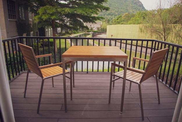 Table et chaise en bois posées sur le balcon de la maison Photo Premium