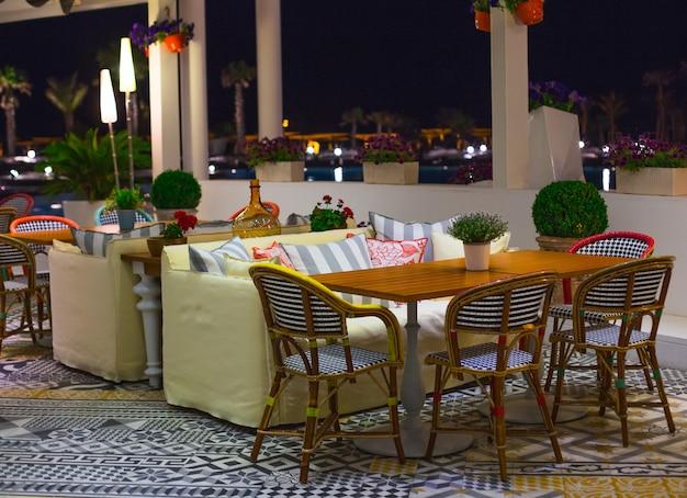 Une table avec des chaises et un canapé jaune dans un restaurant avec vue panoramique. Photo gratuit