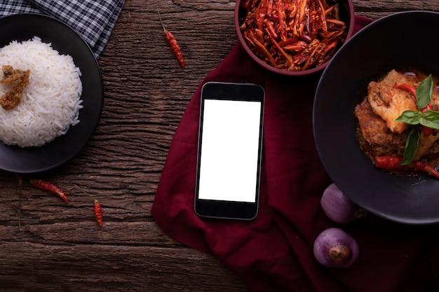 Table de cuisine avec écran blanc sur smartphone, tablette, téléphone portable et curry de porc rouge séché à la noix de coco. Photo Premium