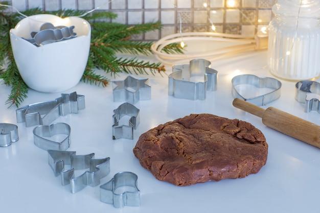 Sur la table de la cuisine pâte de gingembre, rouleau à pâtisserie, branches de sapin, farine, guirlande - préparer les vacances Photo Premium