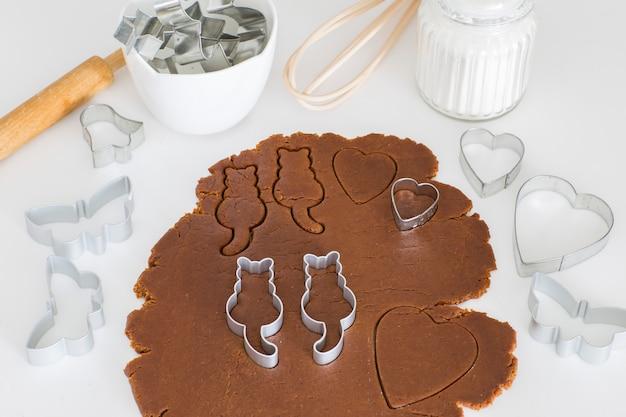Sur la table de la cuisine, de la pâte de gingembre roulée, des emporte-pièces en forme de chat - journée mondiale des chats Photo Premium
