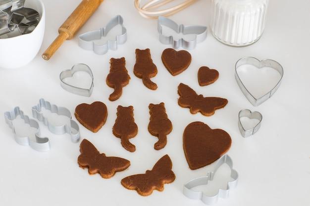 Sur la table de la cuisine sont sculptés à partir de papillons, chats, coeurs de pâte de gingembre Photo Premium