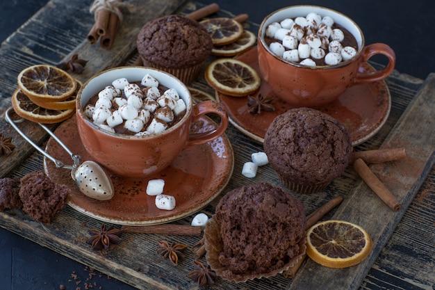 Sur la table, deux tasses de cacao chaud et de guimauves, des muffins au chocolat et un décor Photo Premium