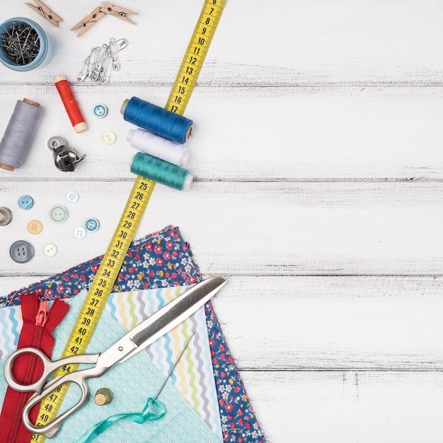 Table avec fournitures de couture et espace de copie Photo gratuit